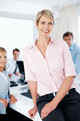 Buy stock photo Portrait of a smiling young businesswoman sitting on the desk and her colleagues working behind at office