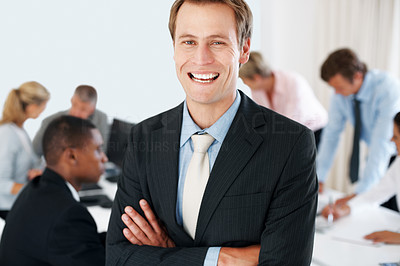 Buy stock photo Smart young businessman laughing with his hands folded and his colleagues working behind at office