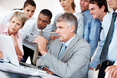 Buy stock photo Mature businessman giving presentation to colleagues on laptop at office