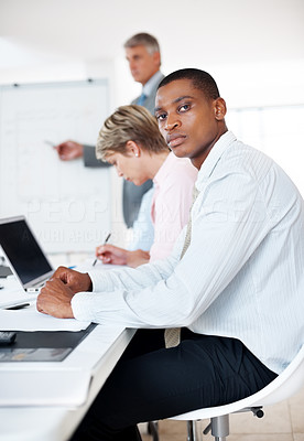 Buy stock photo An african american young businessman attending a presentation with his colleagues