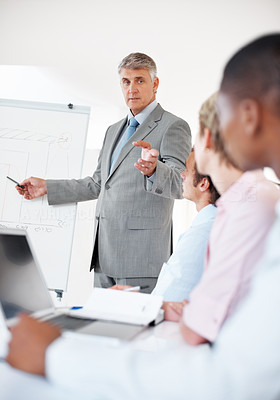 Buy stock photo Portrait of a confident senior manager giving presentation to his colleagues at office