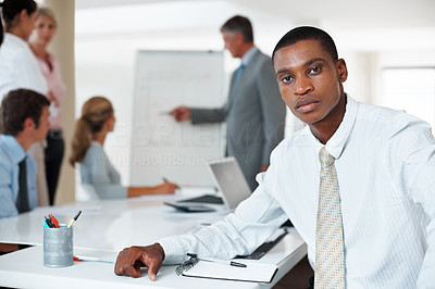 Buy stock photo Portrait of a young businessman looking with an attitude and his colleagues working on presentation at the back