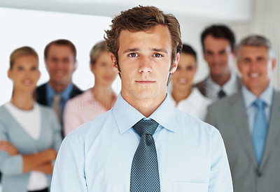 Buy stock photo Portrait of a confident young businessman standing with group of colleagues at the back