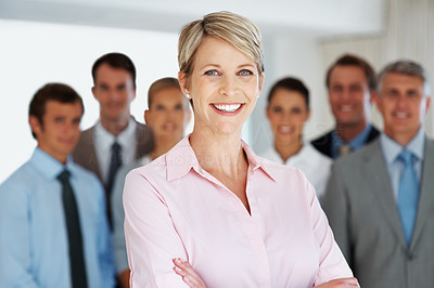 Buy stock photo Portrait of a smart young businesswoman smiling with her colleagues standing behind at office