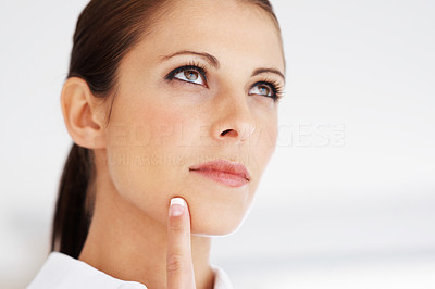 Buy stock photo Closeup portrait of a thoughtful young woman looking up at copyspace