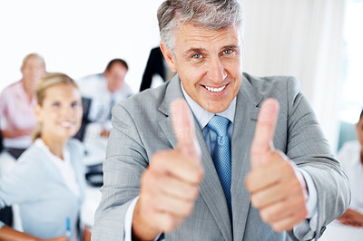 Buy stock photo Portrait of a senior executive gesturing goodluck sign and his team working behind at office