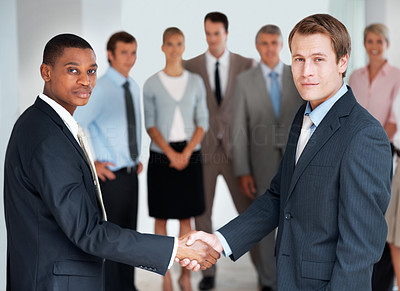 Buy stock photo Multiracial handshake between two business men over a deal in front of colleagues at office