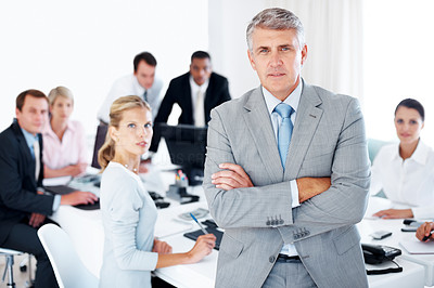 Buy stock photo Confident middle aged businessman standing in office with colleagues in the background
