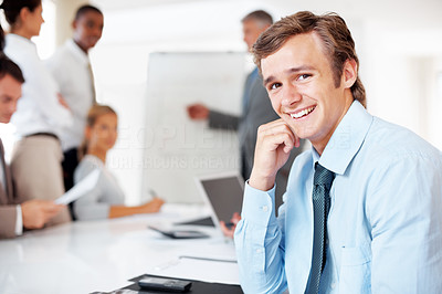 Buy stock photo Portrait of a happy young businessman smiling while attending a presentation at office