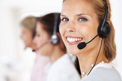 Buy stock photo Closeup portrait of a happy young call center employee wearing headset  with her colleagues in background
