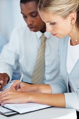Buy stock photo Portrait of a successful young businesswoman taking down notes with her colleague at a meeting