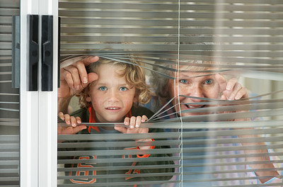 Buy stock photo Portrait of a senior woman and her grandson peeping through a window
