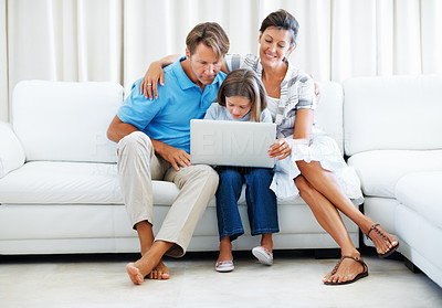 Buy stock photo Full length of daughter sitting on a sofa with her parents and using laptop