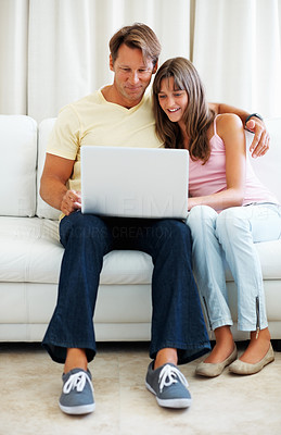 Buy stock photo Full length of father and daughter sitting on a sofa using laptop