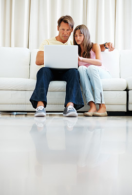 Buy stock photo Full length of father and daughter sitting on a sofa and browsing internet on laptop - copyspace