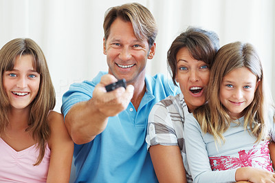 Buy stock photo Portrait of smiling family watching television with man changing channels using remote control