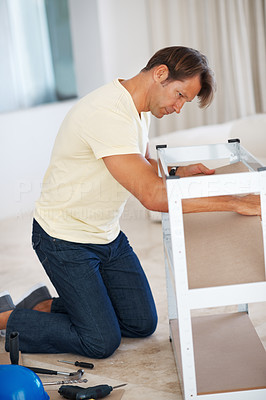 Buy stock photo Man constructing a shelf at home with tools lying on the floor