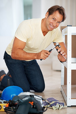 Buy stock photo Portrait of man using hammer and screw driver to build a shelf