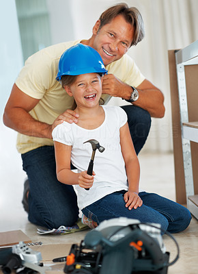 Buy stock photo Father putting a helmet on his daughter while teaching her how to build a shelf