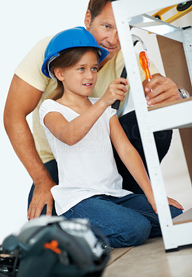 Buy stock photo Man assisting his daughter in using hammer while building a shelf