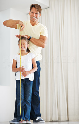 Buy stock photo Full length of man measuring the height of his daughter using a measuring tape