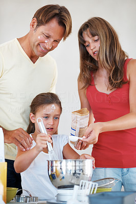 Buy stock photo Young girl whisking flour with father and elder sister assisting her