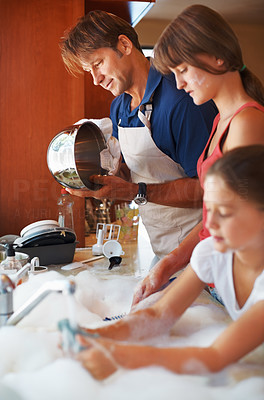 Buy stock photo Man cleaning up the dishes in the kitchen with his daughters