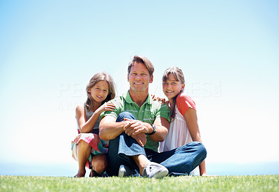 Buy stock photo Full length of father and his two daughters sitting in the grass and smiling - copyspace