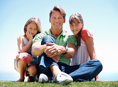Buy stock photo Full length of man sitting on grass with his daughters and smiling