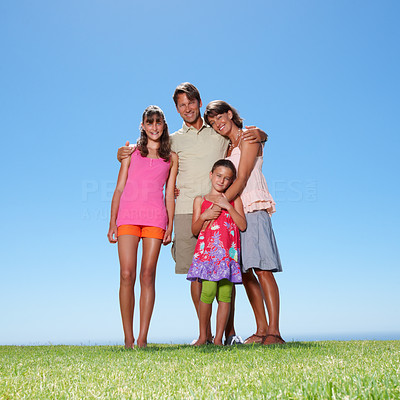 Buy stock photo Full length of happy family of four standing on grass and smiling