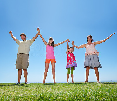 Buy stock photo Full length of family of four holding hands and celebrating outdoors - copyspace