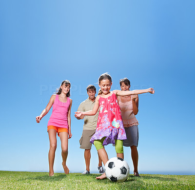 Buy stock photo Full-length of young girl kicking a football with her family running in the background