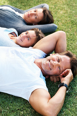 Buy stock photo Closeup portrait of man relaxing on grass with daughter and wife in background