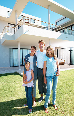Buy stock photo Full length of family standing in front of home and smiling