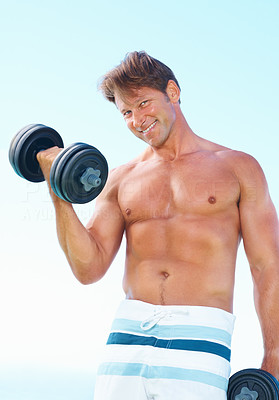 Buy stock photo Portrait of man in shorts standing against sky lifting weights and smiling