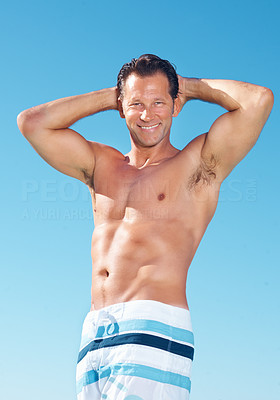 Buy stock photo Portrait of fit muscular man in shorts standing against sky with hands behind head and smiling
