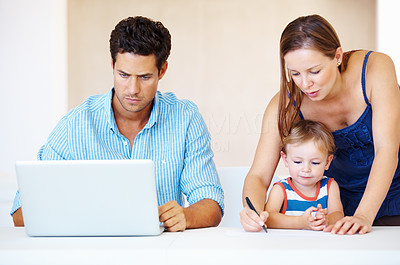 Buy stock photo Family of three sitting at a table with man using laptop and woman writing