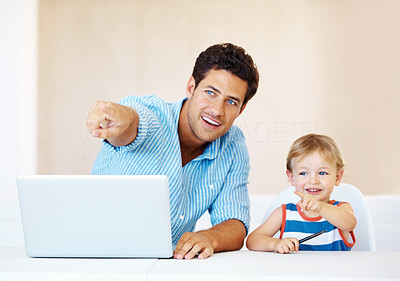 Buy stock photo Father and son sitting at a table using laptop and pointing away