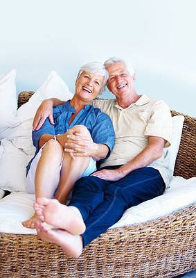 Buy stock photo Portrait of senior couple sitting together on a sofa and smiling