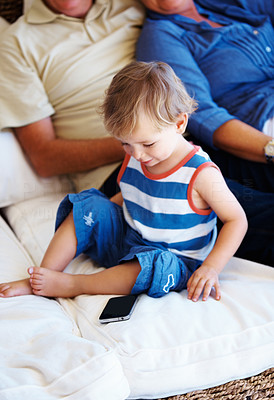 Buy stock photo Young kid sitting on sofa and looking at the mobile phone