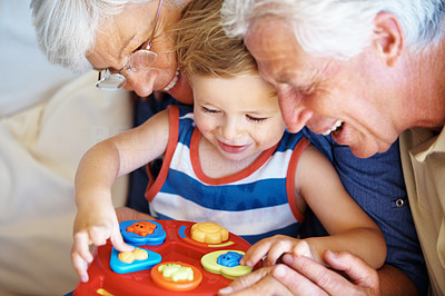 Buy stock photo Young child playing with a toy that his grandparents have just given him - copyspace