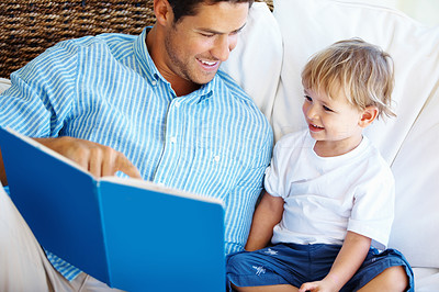 Buy stock photo Family sitting on a sofa with father reading a story to his son