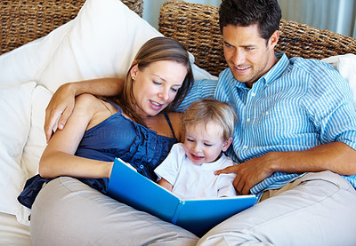 Buy stock photo Family relaxing on a sofa with mother reading a story to her son