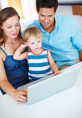 Buy stock photo Cute family of three sitting at a table using laptop