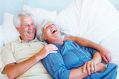 Buy stock photo Senior couple relaxing together on a sofa and having fun