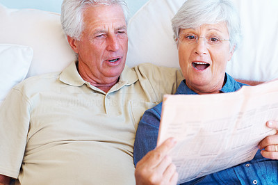 Buy stock photo Senior couple sitting together on sofa with woman reading newspaper