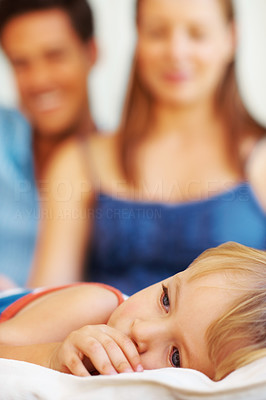 Buy stock photo Closeup of young child lying on down sucking his thumb, with caring parents in the background - copyspace