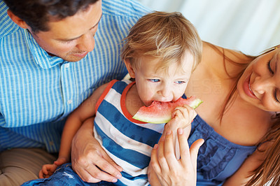 Buy stock photo Closeup of family sitting together with mother feeding watermelon to her child