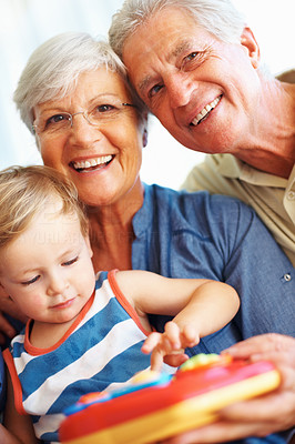 Buy stock photo Portrait of senior couple smiling with grandson playing a toy
