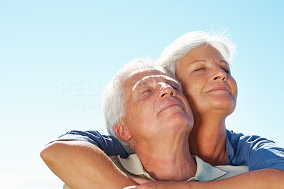Buy stock photo Closeup of senior couple enjoying the serene weather with woman embracing man from behind